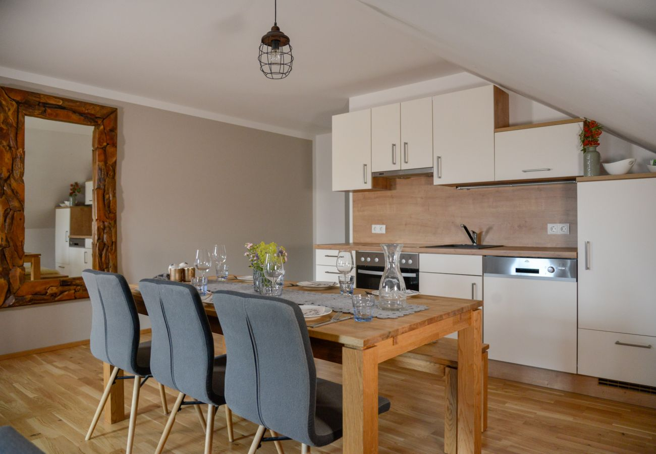 Kitchen with dining table in the holiday home Grimming Lodge Windroeschen in Tauplitz