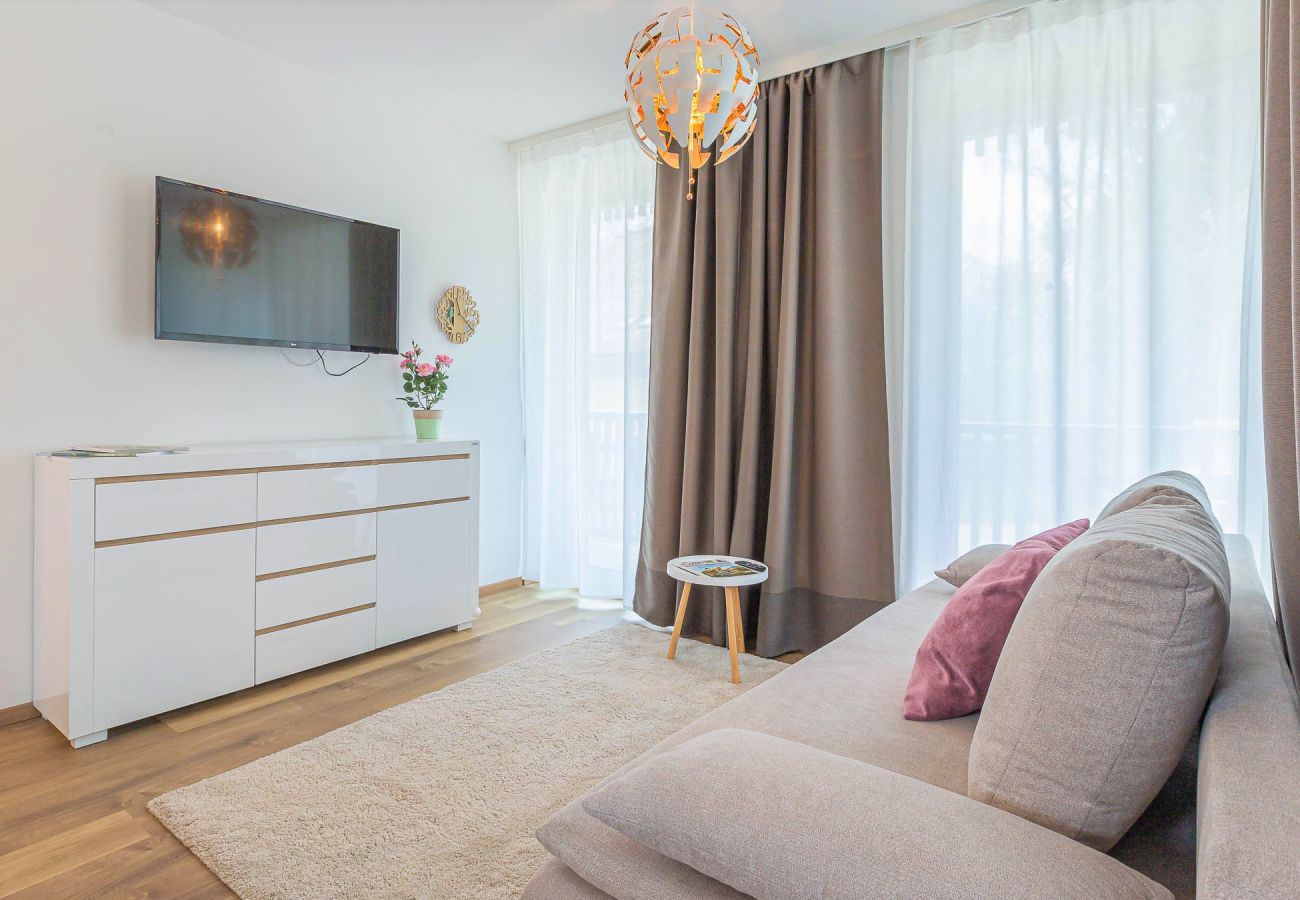 living room with view to the sofa for two persons in Holiday Home Distel in Tauplitz