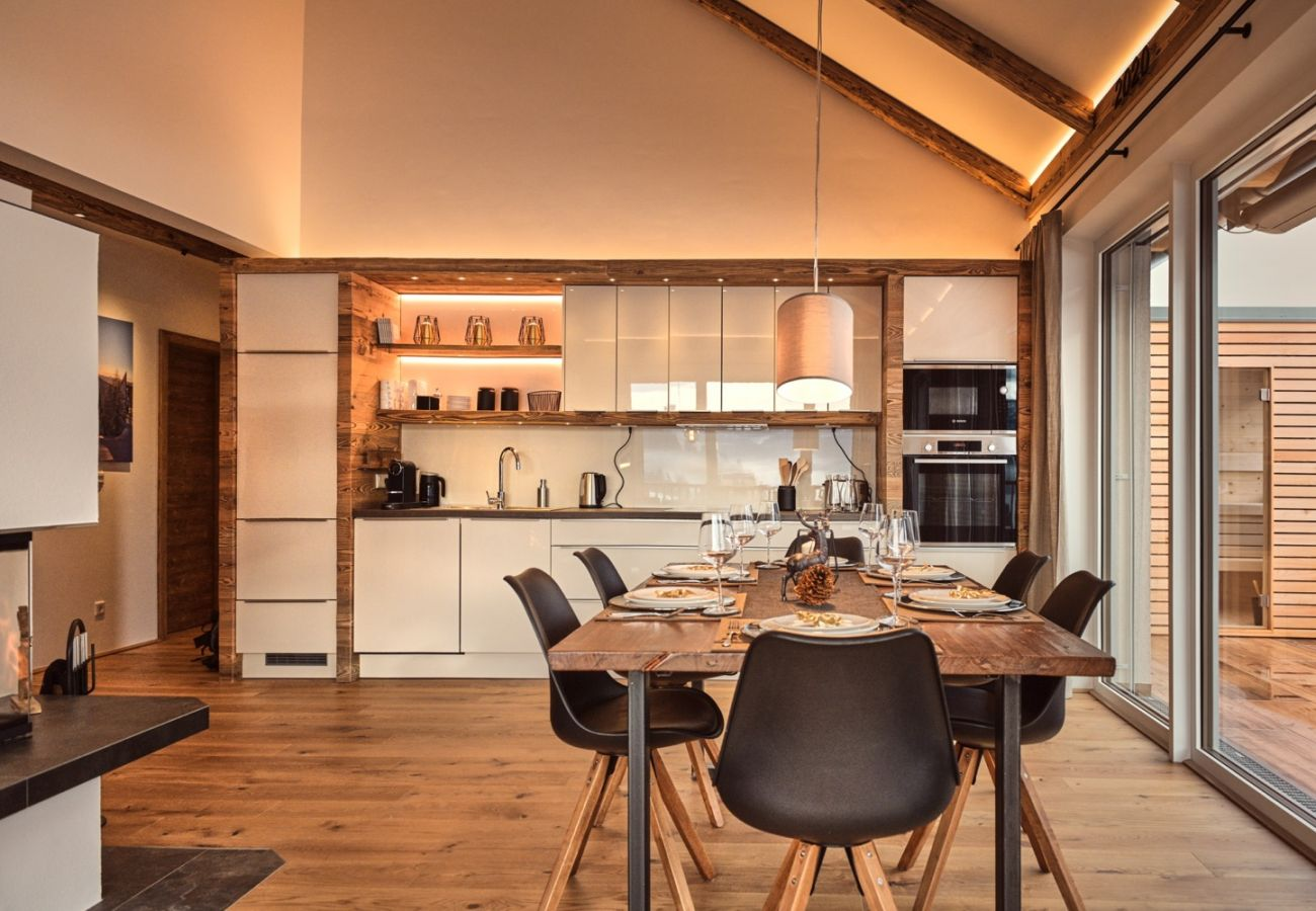 Kitchen with dining table in the holiday home flat Penthouse Grimming Adler Lodge D7.1 in Tauplitz