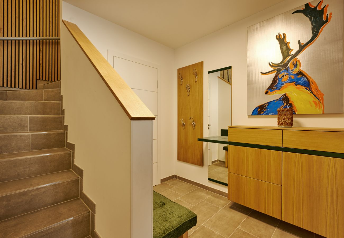 Entrance area with a cloakroom and stairs leading up to the holiday flat Adler Auszeit Lodge D6 in Tauplitz