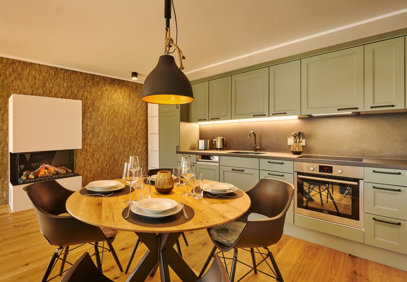 Kitchen with dining table in the holiday home flat Adler Auszeit Lodge D6 in Tauplitz