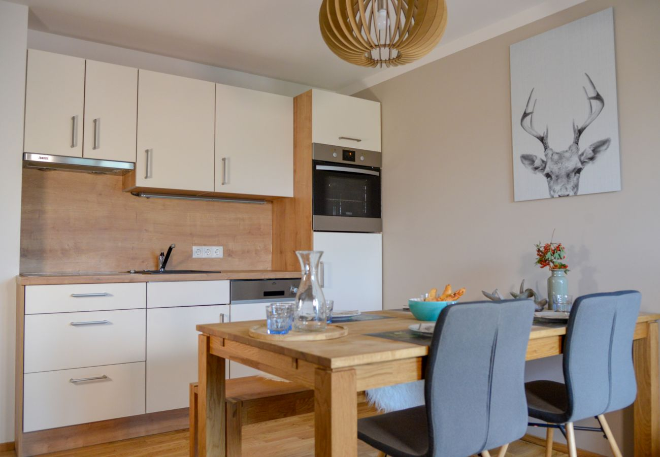Kitchen with dining table in the holiday home Grimming Lodge Goldrute in Tauplitz