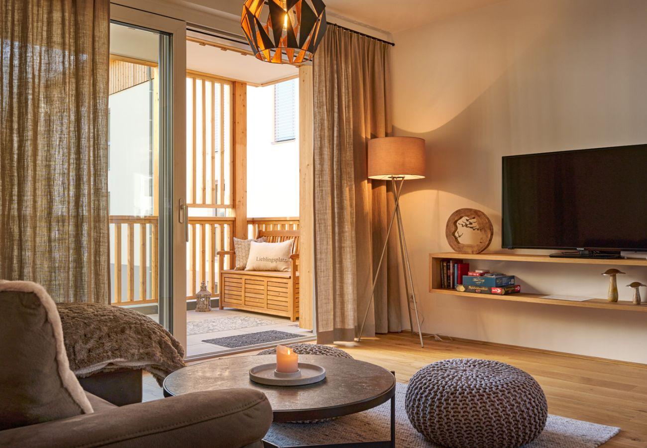 Wohnzimmer mit Fernseher und Blick auf die Berge im Ferienwohnung Alm Lodge A5 in Tauplitz