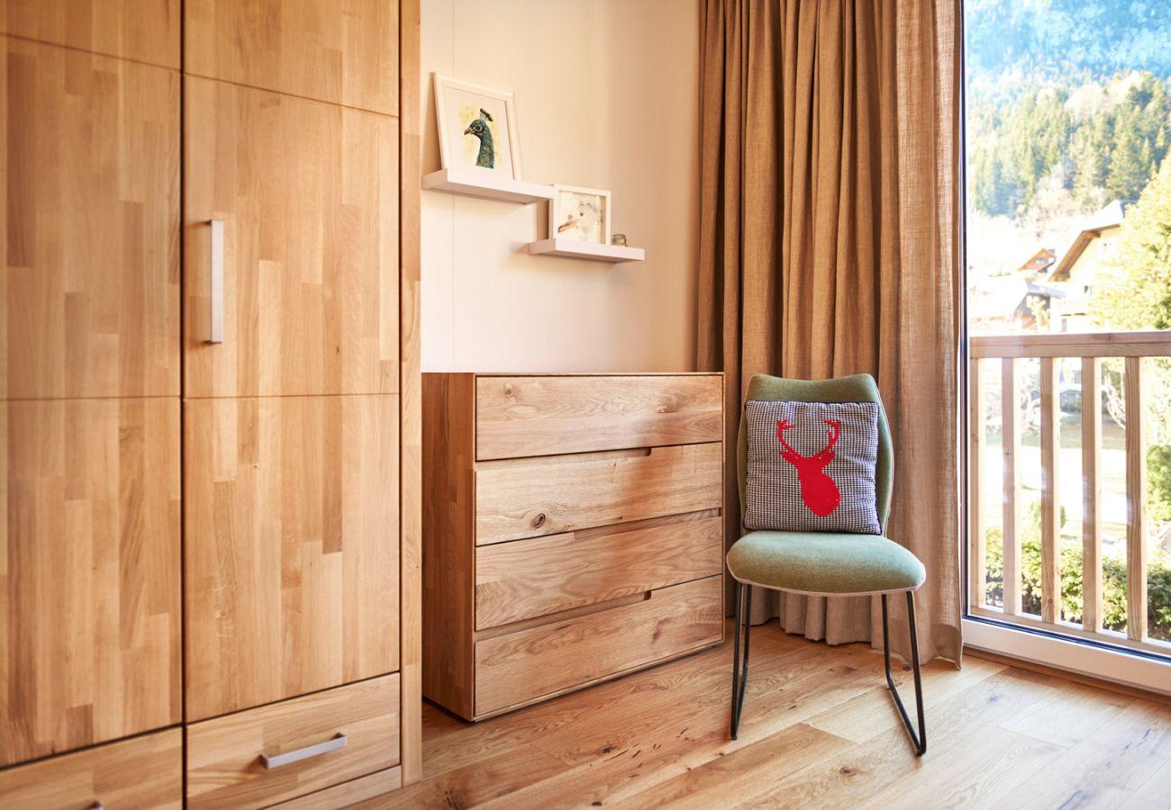 Schlafzimmer 1 mit Kleiderschrank und Sessel in der Ferienwohnung Alm Lodge A5 in Tauplitz