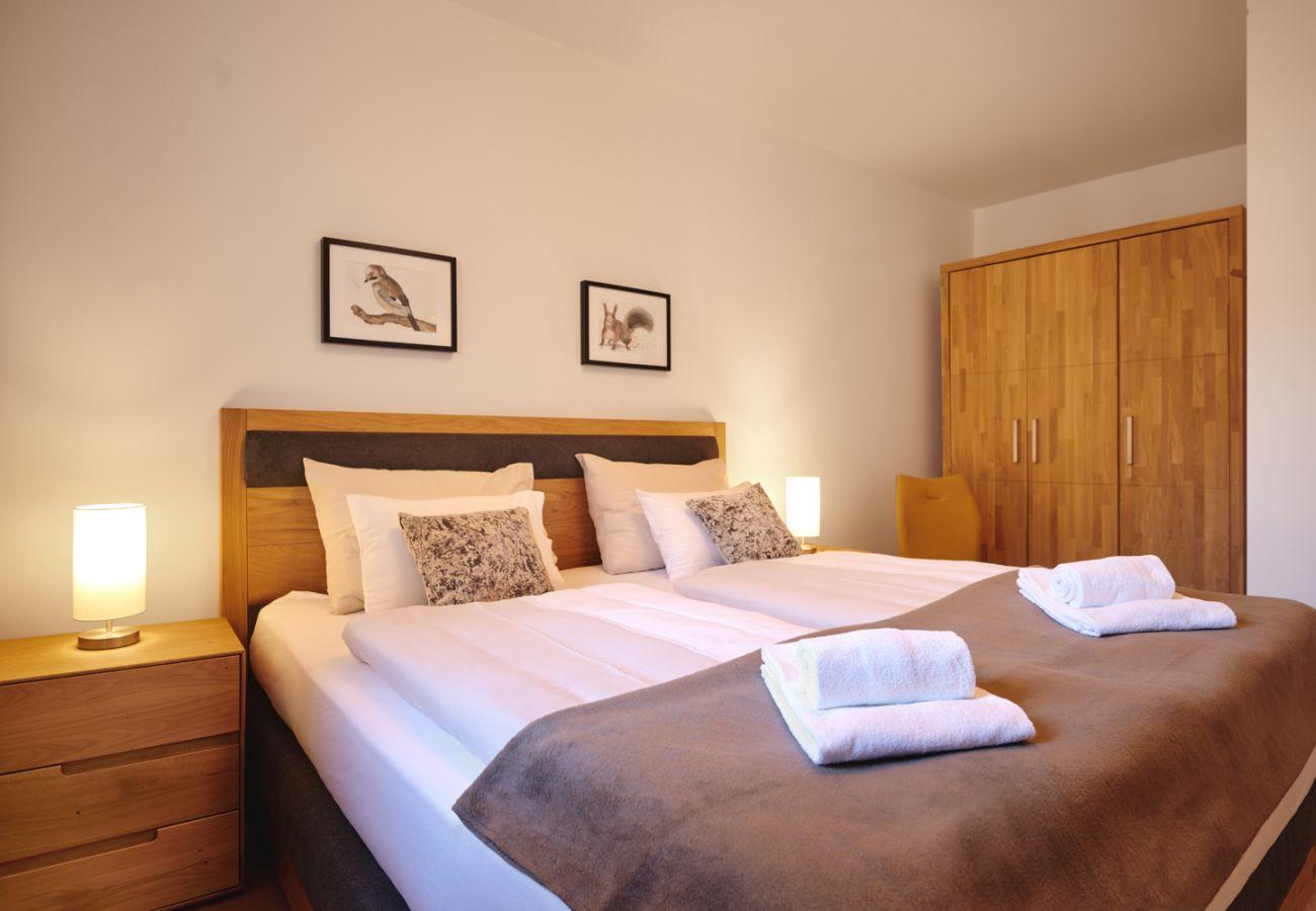 Schlafzimmer 2 mit Kleiderschrank und Sessel in der Ferienwohnung Alm Lodge A5 in Tauplitz