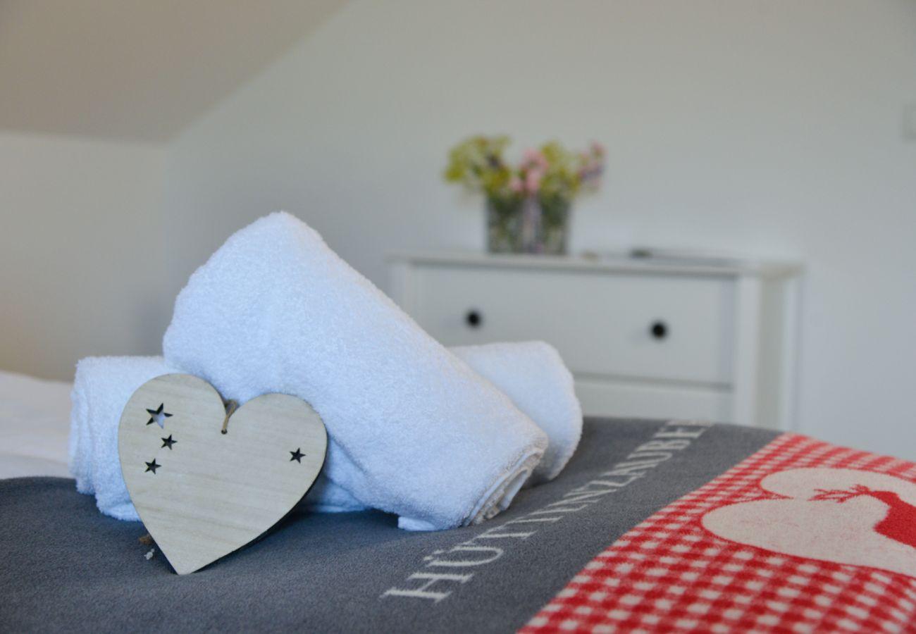 dekoriertes Bett in der Ferienwohnung Grimming Lodge Goldrute in Tauplitz