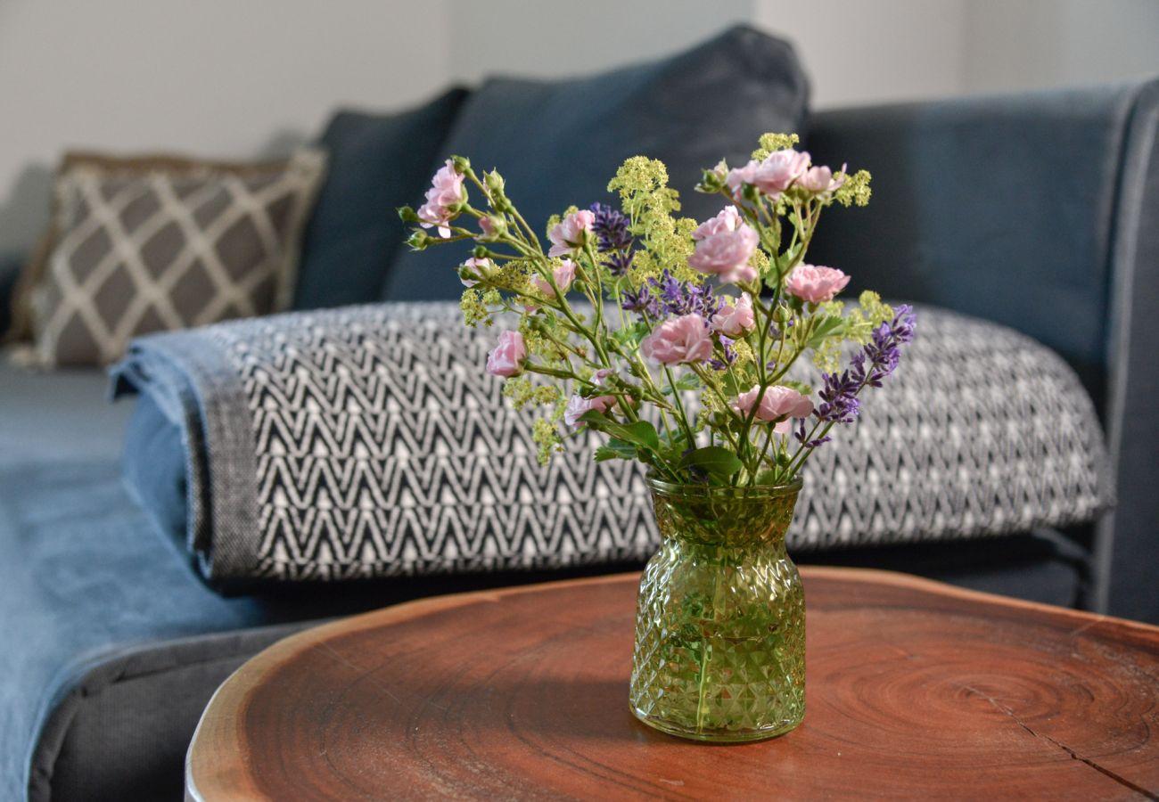 Wohnzimmertisch mit Blumen in der Ferienwohnung Grimming Lodge Goldrute in Tauplitz