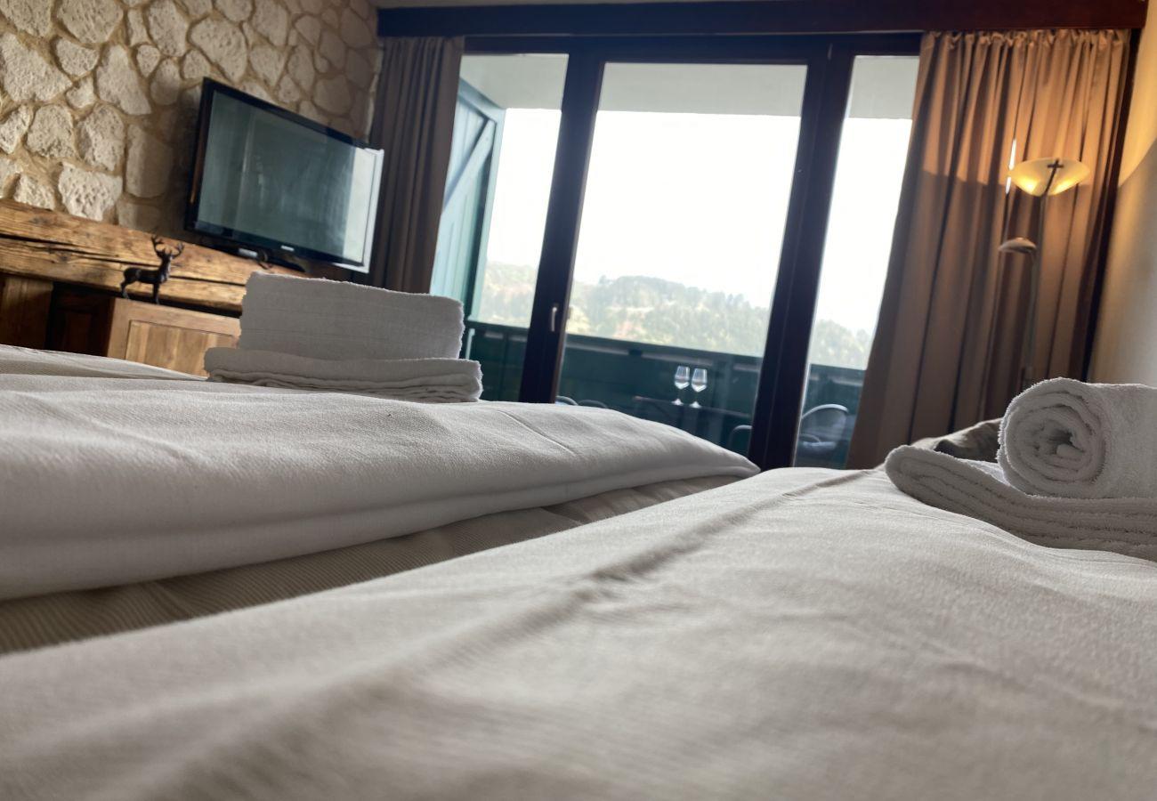 Schlafzimmer mit Aussicht auf die Bergen von der Ferienwohnung Alpine Studio Apartment in der Schladming-Dachstein Region