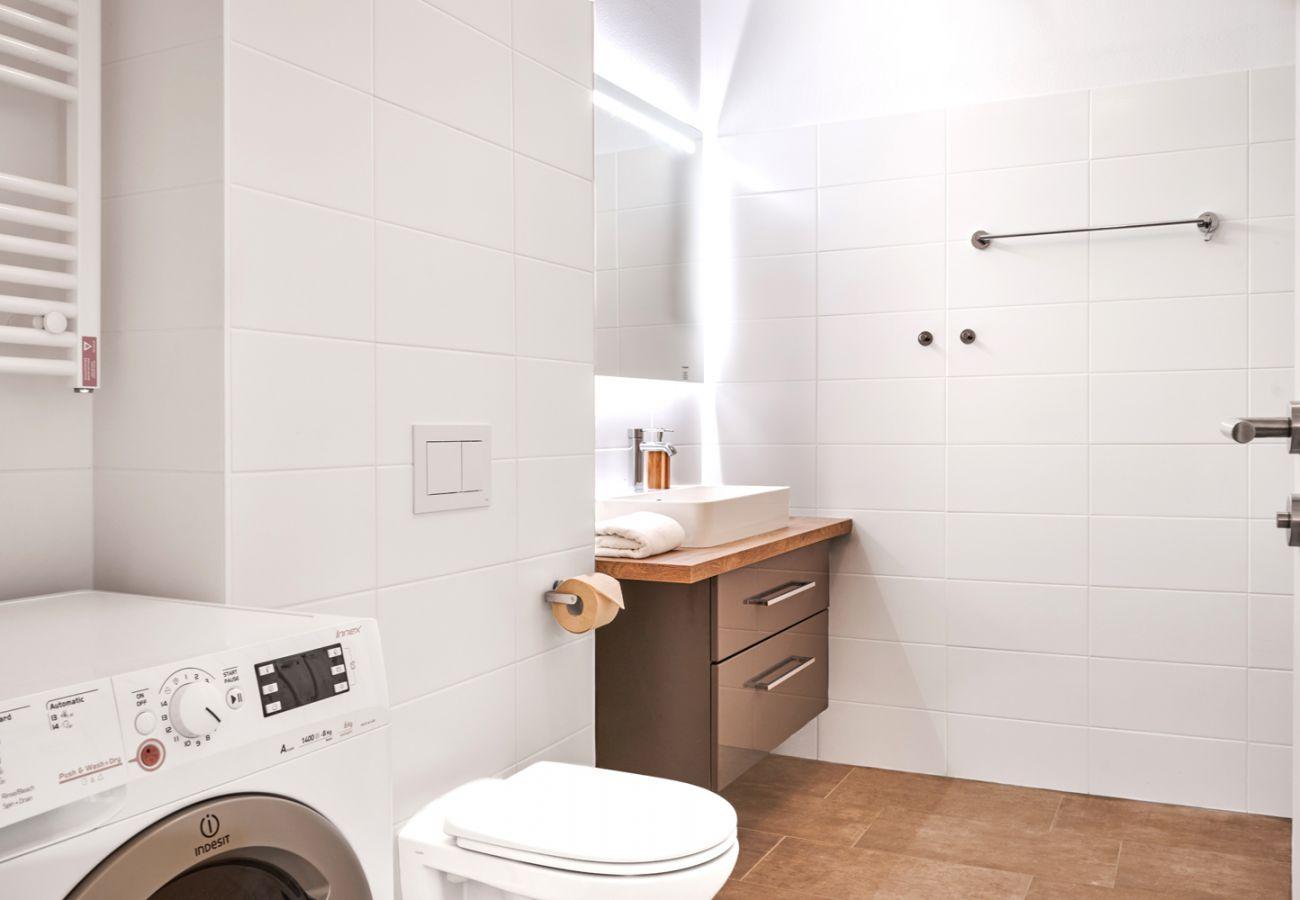 Badezimmer mit Waschmaschine in der Ferienwohnung Adler Lodge D5 in Tauplitz